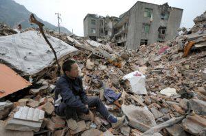 2008年汶川大地震后,幸存者坐在瓦砾堆上。据民间组织巴蜀同盟会调查,这次地震死亡人数约30万人( LIU JIN/AFP/Getty Images)