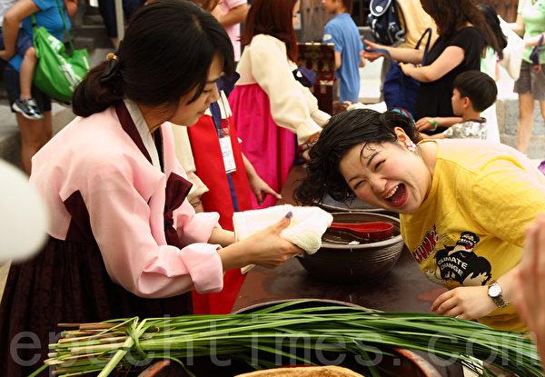 """韩国端午节用菖蒲水洗头,仿佛再现古时""""浴兰汤""""。(全宇/大纪元)"""