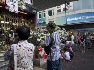 """事发近20天,仍然关闭的太子站B出口处摆满了白色鲜花。18岁的John(图中戴帽子的男孩),站在太子站封闭闸门前默默地撒着纸钱。他不相信警方的""""没人被打死""""之说。(骆亚/大纪元)"""