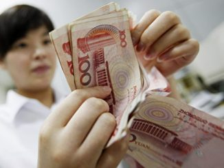 A Chinese bank worker counts stacks of 1
