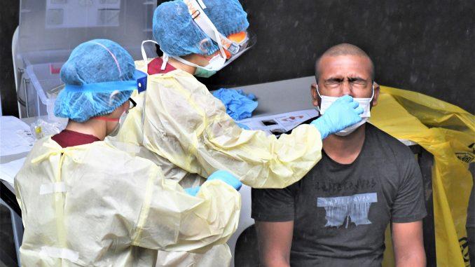 4月27日,本地医护人员正在采集一名客工的鼻拭子样本用于病毒测试