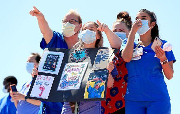 5月6日在美国德州达拉斯,美国海军蓝天使飞行队在空中飞过,向美国对抗中共病毒疫情的医护人员致敬。图为观看飞行表演的医护者举牌致谢。